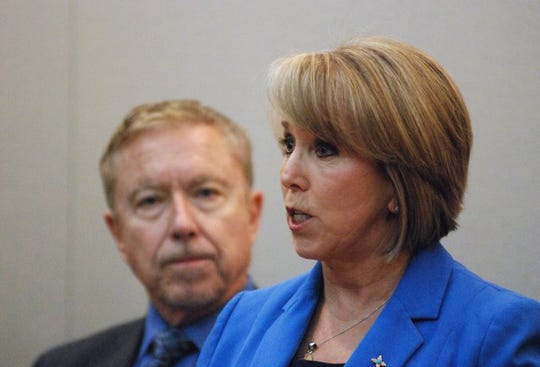 In this Wednesday, March 11, 2020, photo New Mexico Gov. Michelle Lujan Grisham, right, announces a public health emergency in response to the state's first positive tests for COVID-19, at a news conference in Santa Fe, N.M., also attended by Human Services Secretary David Scrase, left. Her administration has banned many gatherings of 100 or more people at spaces such as auditoriums and stadiums as a precaution against the spread of coronavirus. (AP Photo/Morgan Lee)