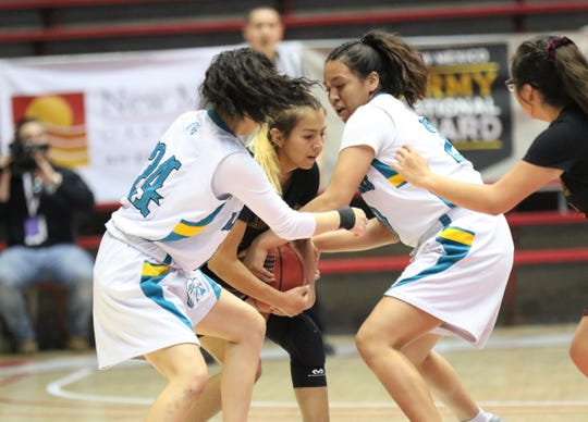 Navajo Prep's Tai Tai Woods (24) and Aiona Johnson (20) smother Tohatchi's Krystal Benally during Friday's 3A girls basketball state championship game at Dreamstyle Arena in Albuquerque.
