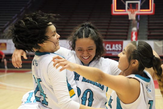 Navajo Prep's Tai Tai Woods (24), Aiona Johnson (20) and Laila Charley (1) embrace each other after defeating Tohtachi 43-33 in Friday's 3A girls basketball state championship game at Dreamstyle Arena in Albuquerque.