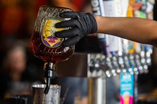 Alejandra Barcenas, a bartender at Big Rock Pub uses gloves as a precaution against coronavirus.