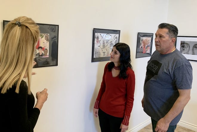 Sandie Newton explores artwork done by Boo2Bullying supporters as Talia Lizemer-Hawley from the Tolerance Education Center and Boo2Bullying founder Dimitri Halkidis look on.