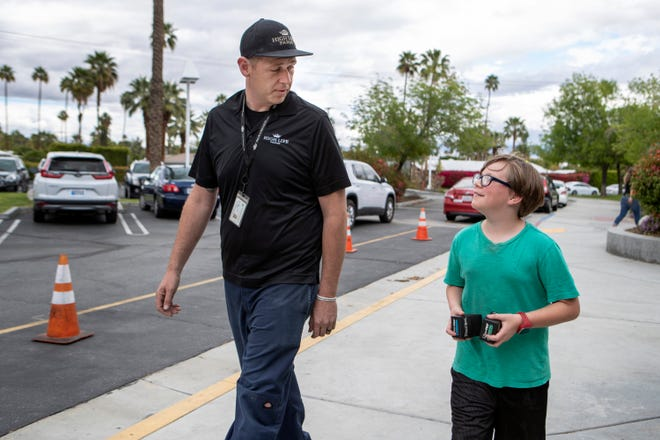 Justin Hagger of Sky Valley picks up his fourth-grade son, Oliver Elmore, at Cahuilla Elementary School in Palm Springs, Calif., on Friday, March 13, 2020. Palm Springs Unified is beginning an early, two-week spring break on Monday.