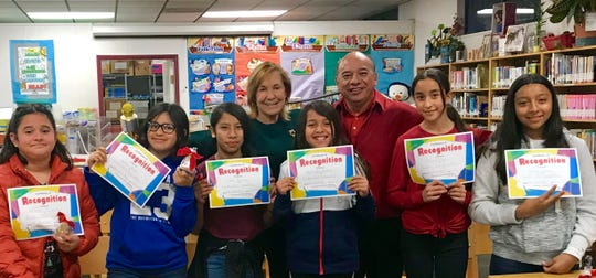 Members of The Writer's Club proudly show off their certificates of recognition.