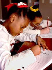 Shrewsbury Elementary School third-grader Christian Dozier, left, and her sister, Tanya, a fifth grader, work on Flexible Instruction assignments at their home in Shrewsbury Township Friday, March 13, 2020. Students in the district were provided with daily Flexible Instruction packets originally intended to minimize the impact of snow days. Southern York County School District canceled classes Friday after a community member was tested for the virus. Bill Kalina photo