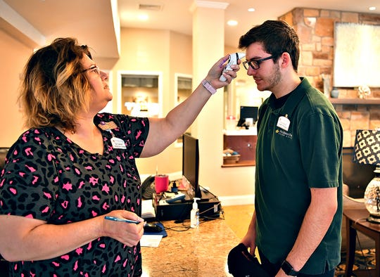 Administrative Assistant Emily Anderson, left, screens employee Tanner Wallace by taking his temperature upon his arrival for his work shift at Providence Place Senior Living of Dover in Dover Township, Friday, March 13, 2020. The senior living facility announced that it will be limiting visitors in the facility in light of the coronavirus pandemic. Dawn J. Sagert photo