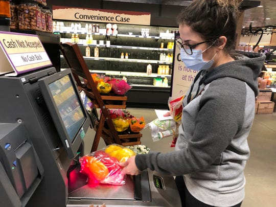 Wearing a surgical mask, Melissa Hall checks out of a Wegmans supermarket March 13 in King of Prussia, Pa.  Gov. Tom Wolf ordered schools, community centers, gyms and other venues in Montgomery County, a Philadelphia suburb, to shut down for two weeks amid a concentration of novel coronavirus cases there.