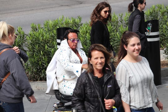 An Elvis impersonator rolls down the Strip on a motorized scooter.