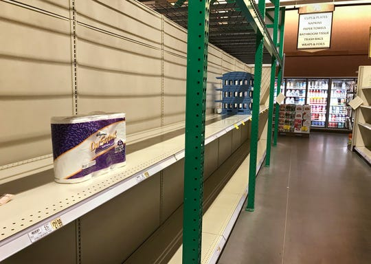 The last package of toilet paper sits on otherwise empty shelves in the Wegmans on East Avenue in Rochester Friday morning, March 13, 2020.