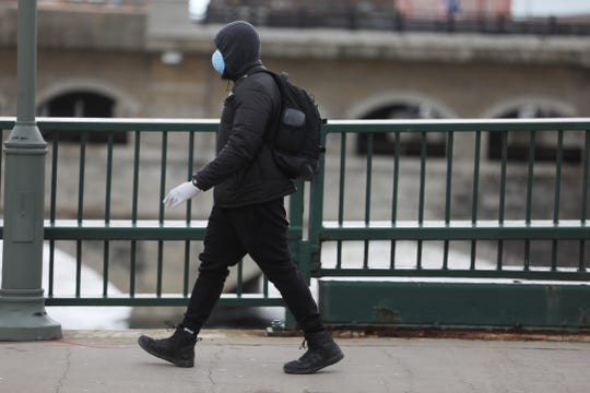 A man walks down Court Street with a mask covering his face and gloves on Friday, March 13, 2020.  Thursday was the first confirmation of Rochester's first positive coronavirus test.