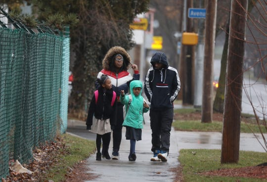 Sisters Madison Hutcherson and Janaee Curry and their parents Bryant Hutcherson and Bernada Curry walk on North St. heading to school at Rochester Prep on March 13, 2020. Many school districts are considering having students stay home and learn on-line as a way to prevent Covid-19.