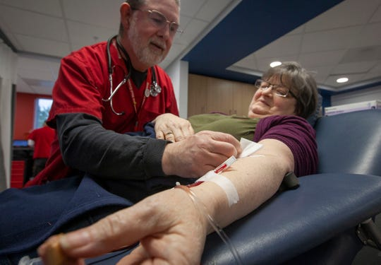 Wendell Stoller, a blood collection tech, left, checks on blood donor Carolyn Stegall, of Salem, as she donates blood March 13, 2020, at the Salem Blood Donation Center at 1860 Hawthorne Ave NE in Salem. The American Red Cross has protocols in place to screen potential blood donors before the enter the facility and encourages people to continue to donate blood.