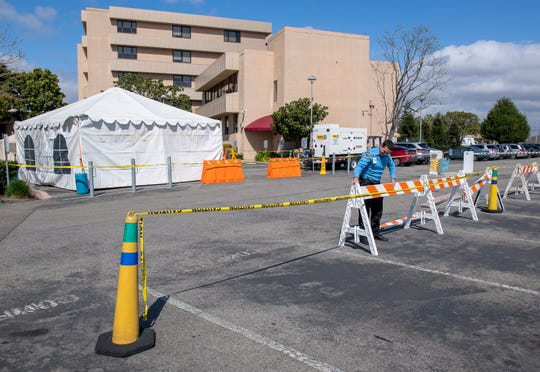 James Mena security officer at the Salinas Valley Memorial Hospital sets up a barricade around the tents that will be used to treat any person dealing with COVID-19. March 13, 2020.
