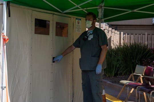 Mitchel Tritt, asistente clínico del Sistema de Salud de Salinas Valley Memorial sujeta su equipo de respirador-purificador a batería mientras trabaja en marzo del 2020 con pacientes que presentan algún síntoma relacionado con el COVID-19.