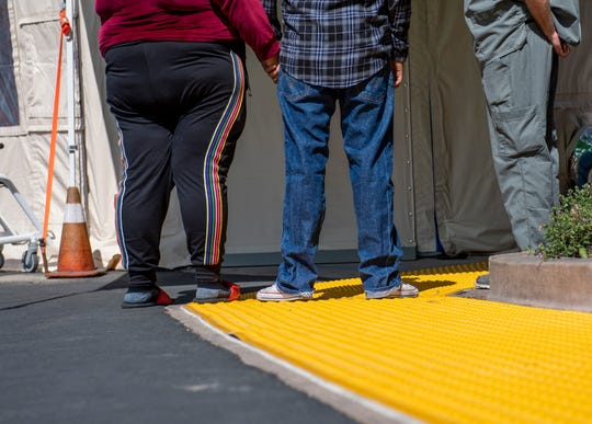 A couple holds hands outside the triage tent as they wait their turn to be tested for possible COVID-19 March 13, 2020.