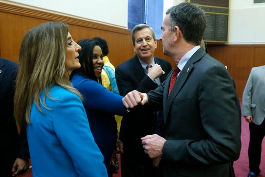 Virginia Gov. Ralph Northam, right, does a elbow bump greeting with House majority leader Charniele Herring, D-Alexandria, second from left, and Delegate Richard Sullivan, D-Arlington, second from right, as House speaker Eileen Filler-Corn, left, looks on at the Capitol Thursday March 12, in Richmond.