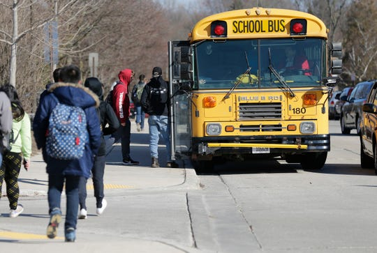 Students enter a waiting bus at Sheboygan North High School, Friday, March 13, 2020, in Sheboygan, Wis.  Gov. Tony Evers today directed Department of Health Services (DHS) Secretary-designee Andrea Palm to issue an agency order mandating the statewide closure of all K-12 schools, public and private, until about April 6, 2020, as part of the state's efforts to respond to and contain the spread of COVID-19 in Wisconsin.