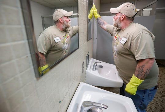 Quinton Forester cleans the men's bathroom at the Veteran's Coming Home Center on Friday, March 13, 2020. The staff were doing a deep cleaning in an effort to prevent an outbreak of the COVID-19 virus in the homeless community.