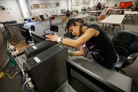 Faith Ramos wipes down a computer at the Veterans Coming Home Center on Friday, March 13, 2020. The staff were doing a deep cleaning in an effort to prevent an outbreak of the COVID-19 virus in the homeless community.