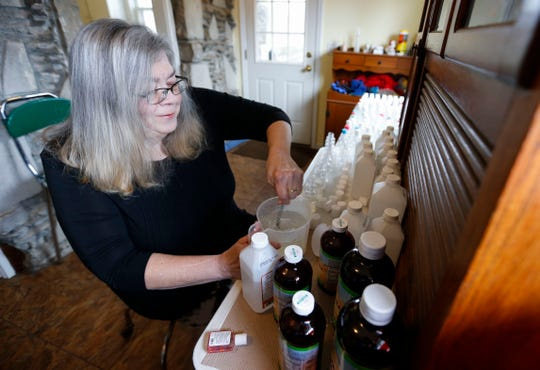Homeless advocate Marti Knaur mixes isopropyl alcohol and aloe vera gel to make hand sanitizer for Springfield's homeless population on Friday, March 13, 2020.
