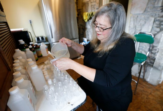 Homeless advocate Marti Knaur pours homemade hand sanitizer, made from isopropyl alcohol and aloe vera gel, into little bottles for Springfield's homeless population on Friday, March 13, 2020.