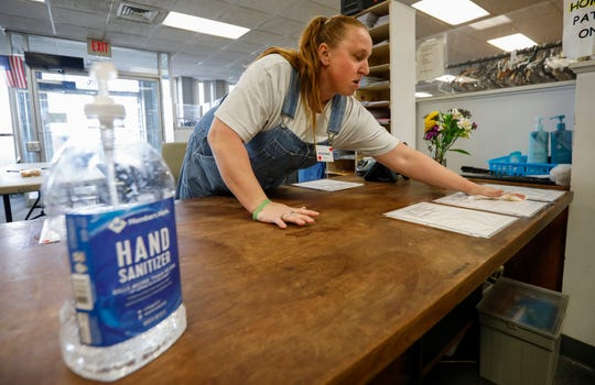 Rosemary Forester wipes down a desk at the Veterans Coming Home Center on Friday, March 13, 2020. The staff were doing a deep cleaning in an effort to prevent an outbreak of the COVID-19 virus in the homeless community.