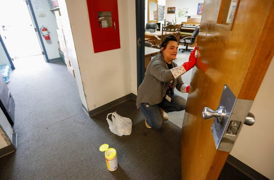 Alisha Seefeldt cleans a door with a disinfectant wipe at the Veterans Coming Home Center on Friday, March 13, 2020. The staff were doing a deep cleaning in an effort to prevent an outbreak of the COVID-19 virus in the homeless community.