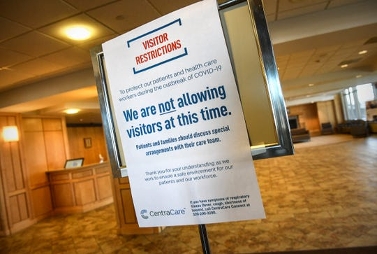 A sign lists the visitor's policy Friday, March 13, 2020, at an entrance to St. Cloud Hospital.