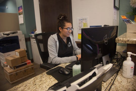 Mia Ramirez, a receptionist at the St. George Family Health Center, checks in patients Friday, March 13, 2020.