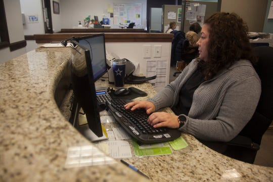 Adriana Ceja, a receptionist at the St. George Family Health Center, records patient information Friday, March 13, 2020.