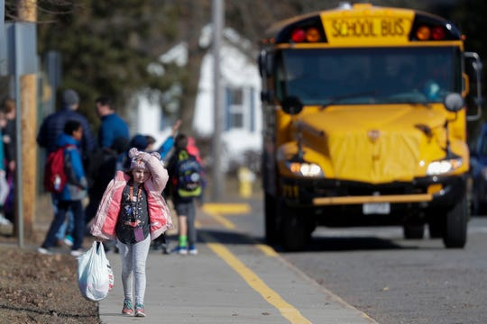 A student leaves school at the end of the day on Friday, March 13, 2020, at Washington Elementary School in Stevens Point, Wis. The Stevens Point Area School District announced Friday that it is canceling school through March 29 due to concerns of COVID-19.