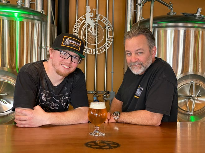 Head brewer David Chaney, left, and co-owner Brad Cristea pose behind the counter at Pedals & Pints Brewing Co. in Thousand Oaks. The bicycling-themed craft brewery will mark its grand opening on March 17.