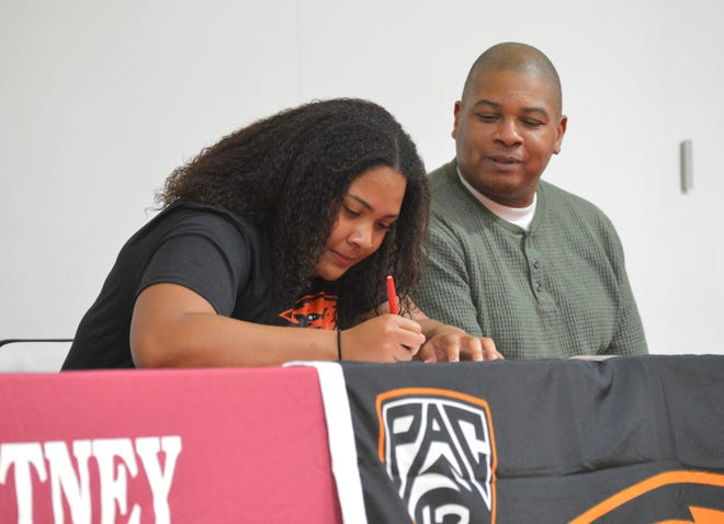 Mt. Whitney High senior Jade Whitfield, left, signs her letter of intent on Thursday to extend her track and field career at Oregon State.