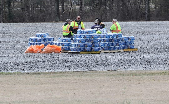 A group of workers sit next to a pile of bottle water in the parking field at Anthony Wayne Recreation Area in Bear Mountain, New York Friday March 13, 2020.