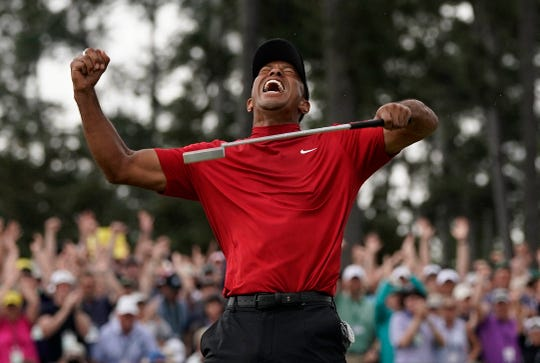 Tiger Woods reacts after winning the 2019 Masters tournament in Augusta, Ga. The first major championship of the season is being postponed over concerns about the spread of COVID-19.