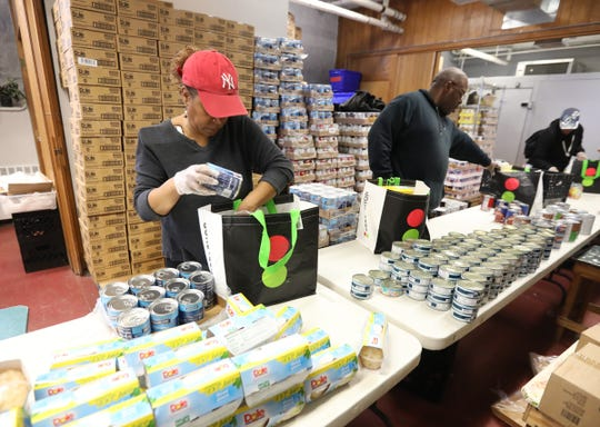 Volunteers Sylvia Hamer, left, and Howard Gray pack bags of non-perishable goods donated by Stop & Shop at the Hope Community Food Pantry in New Rochelle on Friday, March 13, 2020.