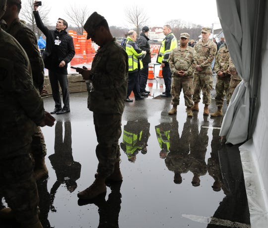 Members of the New York National Guard listen to remarks by Gov. Andrew Cuomo at Glen Island Park in New Rochelle, as New York State's first drive through COVID-19 mobile testing center opens, March 13, 2020.
