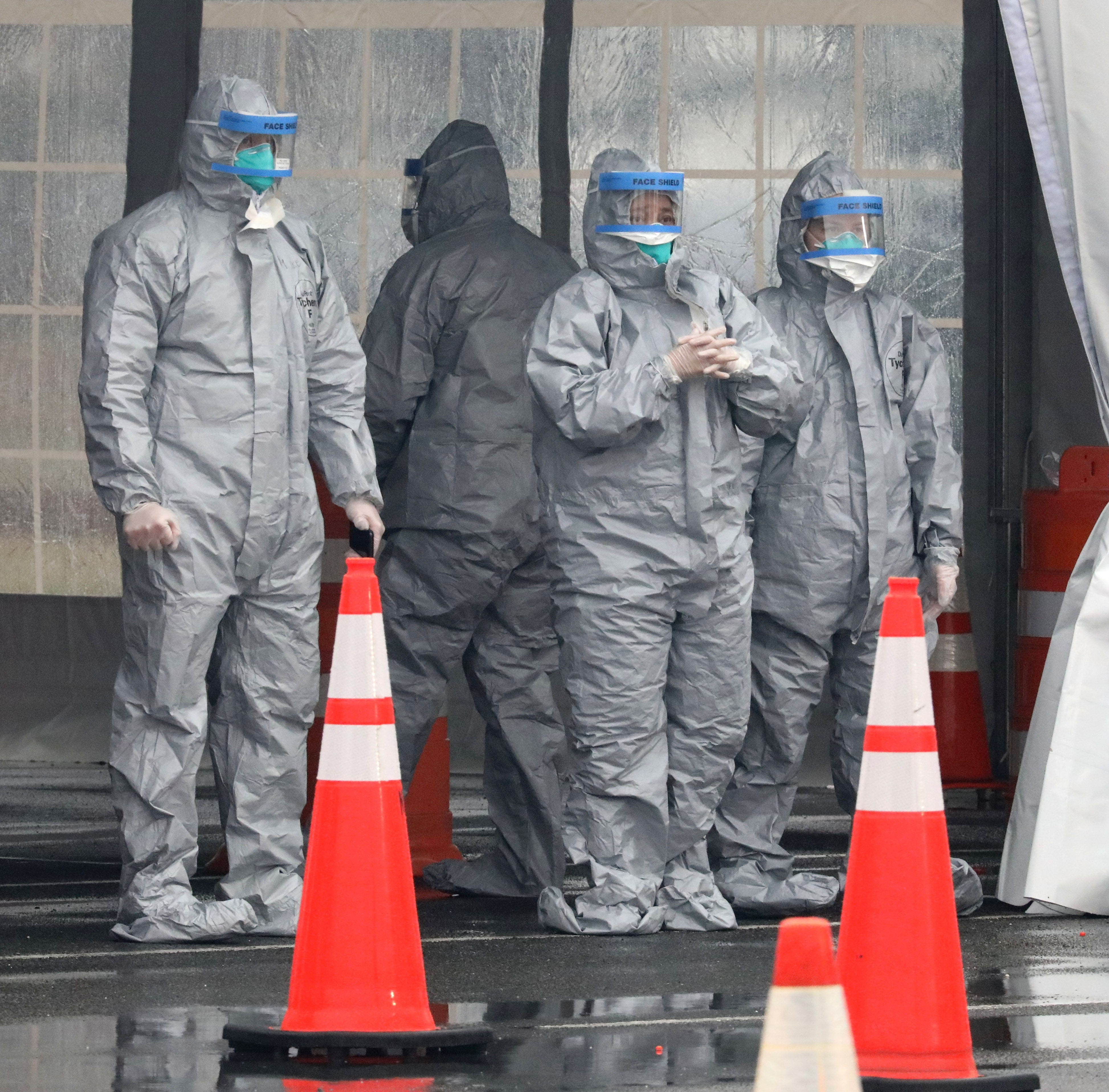 Workers in protective clothing wait for cars to arrive at Glen Island Park in New Rochelle, as New York State's first drive through COVID-19 mobile testing center opens, March 13, 2020.