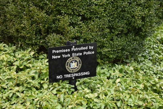 A sign in the pachysandra alerts visitors that the home of the governor's former girlfriend has State Police security.