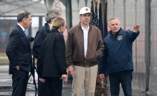 New York Governor Andrew Cuomo, in hat, gets a briefing from Michael Kopy, the NYS Director of Emergency Management, at Glen Island Park in New Rochelle, as New York State's first drive through COVID-19 mobile testing center opens, March 13, 2020.