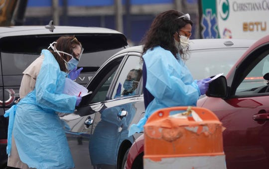 Health care workers with ChristianaCare test people with symptoms of the coronavirus in a drive-thru in the parking lot of Chase Center on Friday. Tests were free, and patients will receive their results in two to five days.