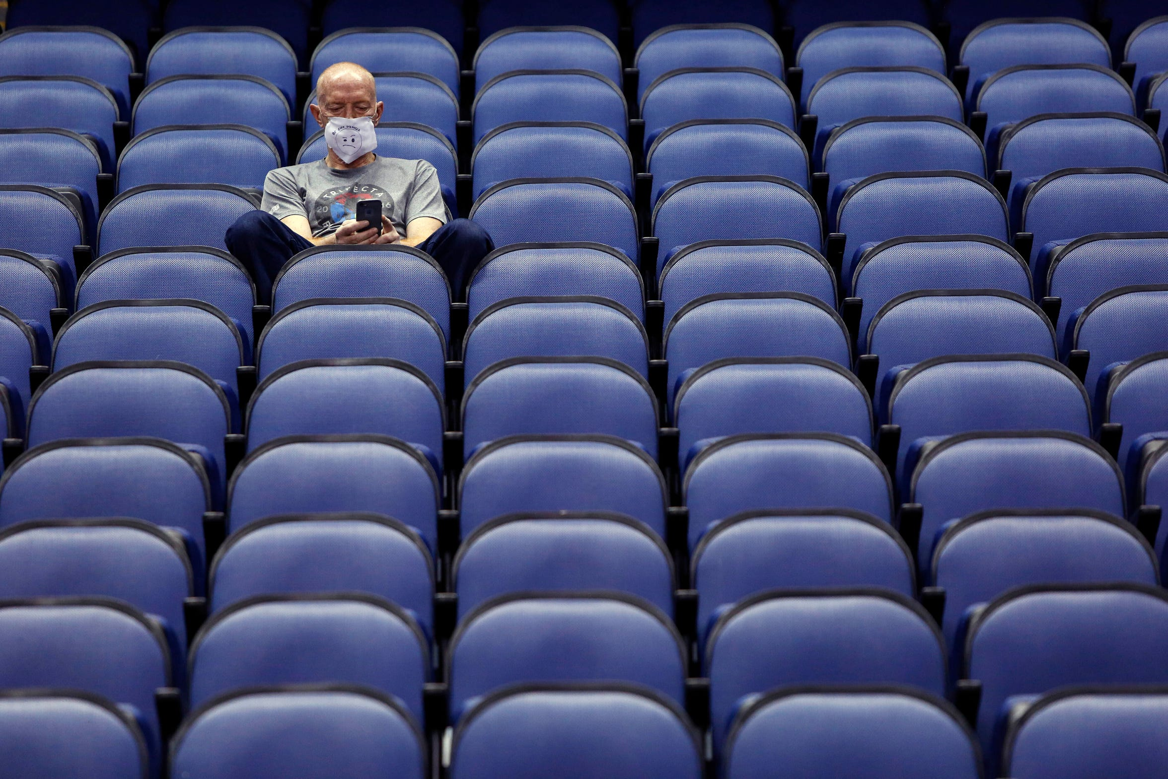 Mike Lemcke, from Richmond, Va., sits in an empty Greensboro Coliseum after the NCAA college basketball games were canceled at the Atlantic Coast Conference tournament in Greensboro, N.C., Thursday, March 12, 2020. (AP Photo/Ben McKeown)