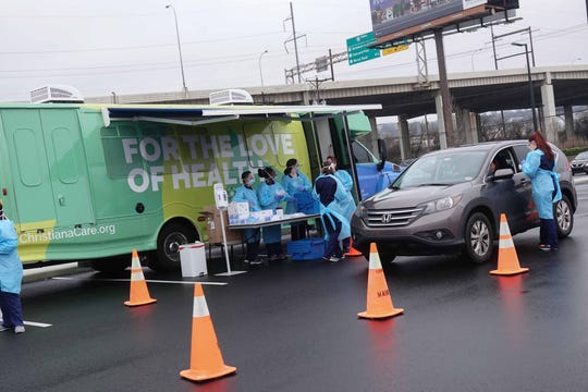 Healthcare workers with ChristianaCare test people with symptoms of the coronavirus in a drive-thru in the parking lot of Chase Center on Friday.