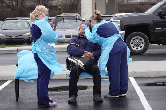 A man is tested for the coronavirus by healthcare workers from ChristianaCare in the parking lot of Chase Center  on March 13.
