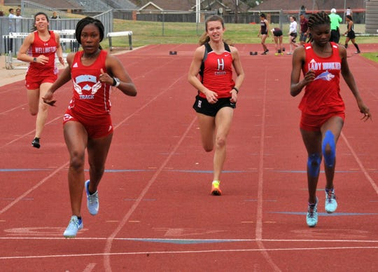 Hirschi's Jada Browning (left) crosses the finish line ahead of teammate Miracle Holmes (right) and Holliday's Sarah Jones during a 100-meters heat at the Wichita Falls Coach's Invitational at Garnett Field on Thursday, March 13, 2020.
