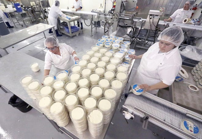Workers at Specialty Cheese Co. package products on the floor of the company's Reeseville, Wis. plant Thursday, Feb. 27, 2020. The company has found its niche manufacturing ethnic cheeses, including those found in Latino, Polish and Middle Eastern cultures.