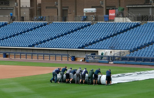 Grounds crew roll up a tarp at an empty American Family Fields stadium, spring training home of the Milwaukee Brewers, following Major League Baseball's decision to suspend all spring training games on March 12, 2020 in Phoenix, Ariz. The decision was made due to concerns of the ongoing Coronavirus (COVID-19) outbreak.