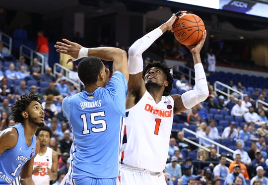 Syracuse forward Quincy Guerrier shoots the ball against North Carolina forward Garrison Brooks during the 2020 ACC tournament at the Greensboro Coliseum.