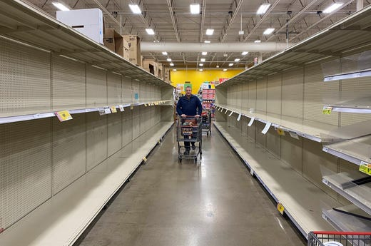 Customers at grocery chain HEB in Austin look for products among increasingly empty shelves as the city responds to concerns of the spread of the new coronavirus and COVID-19 on March 13, 2020.