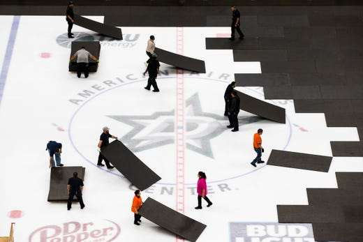Crews cover the ice at American Airlines Center in Dallas, home of the Dallas Stars hockey team, after the NHL season was put on hold due to coronavirus, Thursday, March 12, 2020.