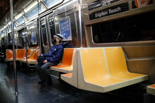A commuter wears a face mask while riding the a nearly empty subway car into Brooklyn on March 12. New York City Mayor Bill de Blasio said Thursday he will announce new restrictions on gatherings to halt the spread of the new coronavirus in the coming days. Broadway shows will be shuttered for at least a few weeks.